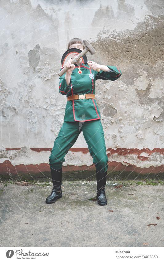 jugendliche in uniform spielt mit sichel und hammer Jugendliche Teenager junge Frau Uniform Soldat Komikerin Spaß seltsam lustig Mensch Karnevalskostüm verrückt