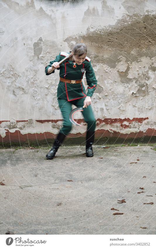 jugendliche in uniform mit sichel und hammer in der hand macht ein seltsames tänzchen Mädchen junge Frau Jugendliche Teenager Pubertät Uniform Anzug Sichel