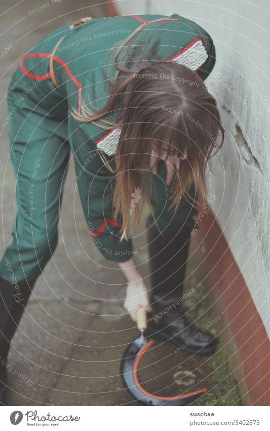 mädchen in uniform versucht unkraut mit einer sichel zu entfernen Mädchen junge Frau Uniform Sichel Werkzeug Waffe Jugendliche Sozialismus Hausmeisterin Hof