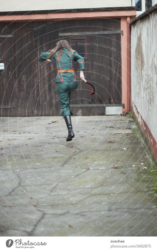 teenager in uniform hüpft mit einer sichel in der hand über im innenhof Mädchen junge Frau Jugendliche Teenager Pubertät Uniform Anzug Sichel Hammer Werkzeug