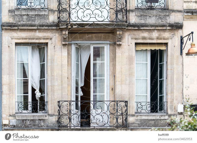 eleganter Altbau Balkon mit offenen Fenstern und wehenden Gardinen Vorhängen Fensterladen Reihe Natursteinfassade Mauer Wand Bogenfenster Zentralperspektive