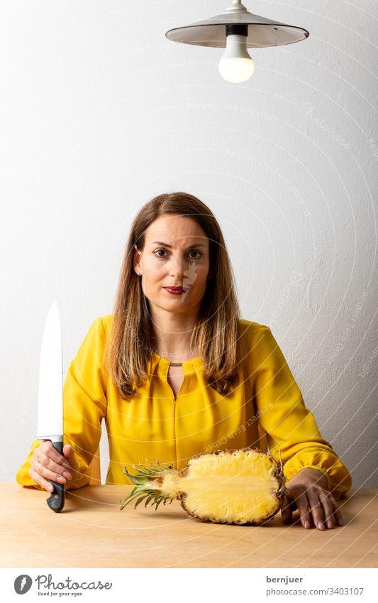 Frau mit Messer am Tisch Brünette Haus Innen Koch Kochmesser Interieur Küche Halb Ananas Kochen Sitzen Lampe Bluse gelb Porträt Holz glücklich Schönheit Produkt