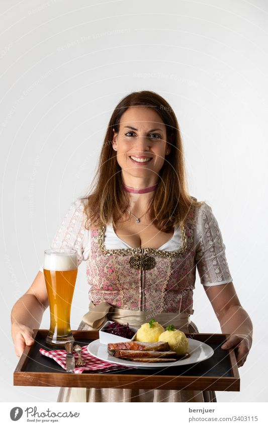 Frau in einem bayerischen Dirndl mit Tablett Abendessen halten weiß isoliert Oktoberfest Schweinebraten Servieren tragen Alkohol Kellnerin tracht Weizenbier
