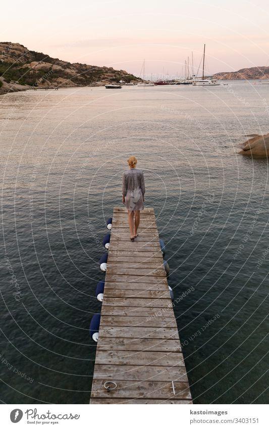 Schöne Frau in luxuriösem Sommerkleid, die auf einem Holzsteg steht und in der Abenddämmerung die friedliche Meereslandschaft genießt. Reisende Frau steht auf einem hölzernen Pier in Porto Rafael, Costa Smeralda, Sardinien, Italien.