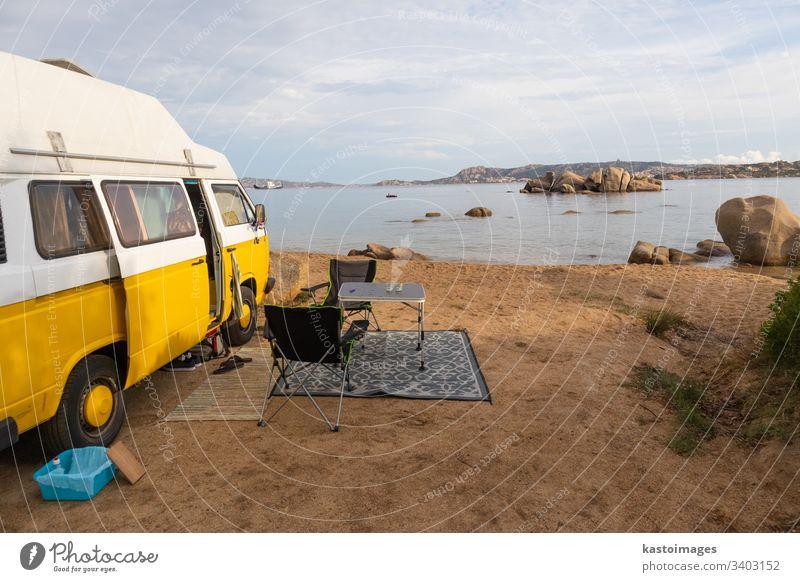 Minivan-Oldtimer auf einem Campingplatz am Strand der Insel Sardinien, Italien. Kleintransporter retro Hippie altehrwürdig Autoreise Lager reisen Ausflug