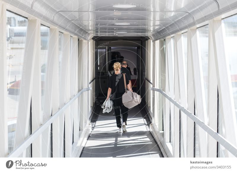 Weiblicher Passagier, der die Handgepäck-Tasche trägt, geht durch den Einstiegskorridor des Flugzeugs. reisen Fluggerät Frau Ebene transferieren Verkehr