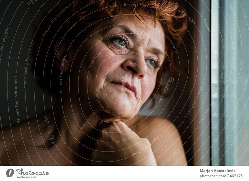 Reife Frau am Fenster, die über das Leben nachdenkt Erwachsener Lebensalter gealtert Alterung allein schön Schönheit Pflege Kaukasier Nahaufnahme betrachtend