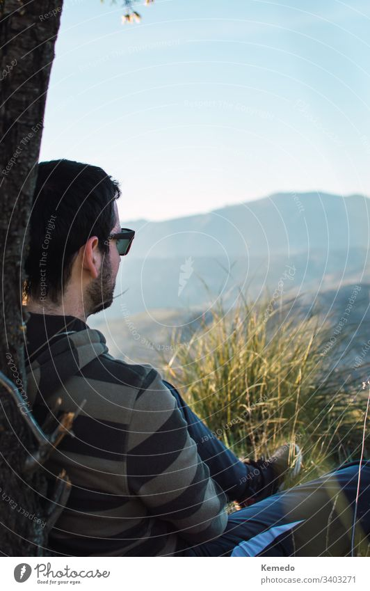 Seitenansicht eines Mannes mit Sonnenbrille, der an einem sonnigen Tag auf dem Gras in der Nähe eines Baumstammes sitzt, mit den Bergen im Hintergrund. sitzen