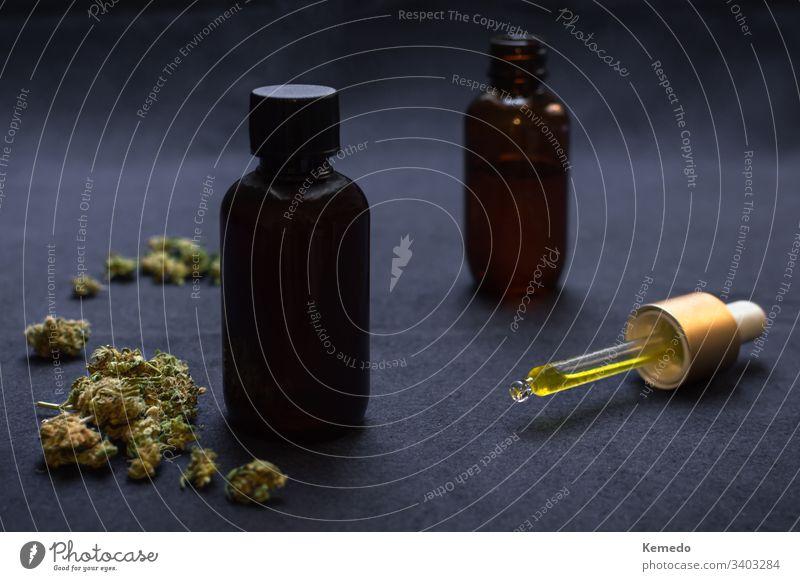Organisches CBD-Öl oder Tinktur mit Cannabis auf schwarzem Grund. Medizinisches Marihuanaprodukt, Unkrautknospen und Tropfer. cbd Erdöl Hintergrund