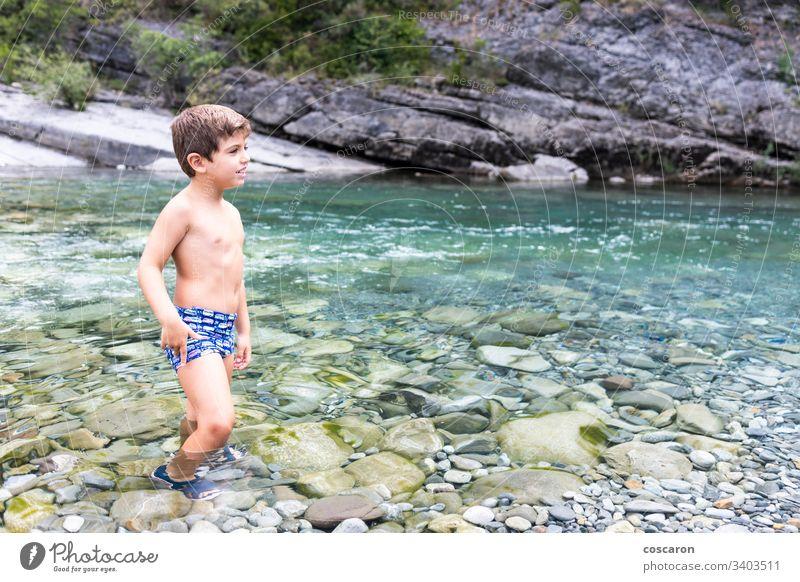 Kleines Kind in der Mitte eines wilden Flusses Aktivität allein heiter Kindheit cinca Küste Überfahrt Tag Genuss fließen Spaß Spiel Mädchen Fröhlichkeit