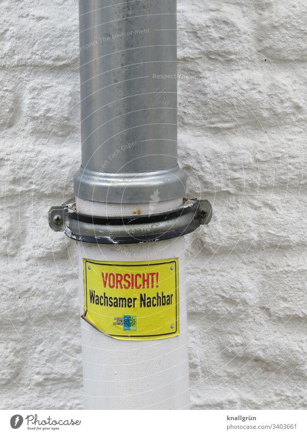 """Fallrohr mit Aufkleber """"Vorsicht! Wachsamer Nachbar""""vor weiß getünchter Hauswand Kommunikation Warnung Hinweisschild Warnschild Schilder & Markierungen"""