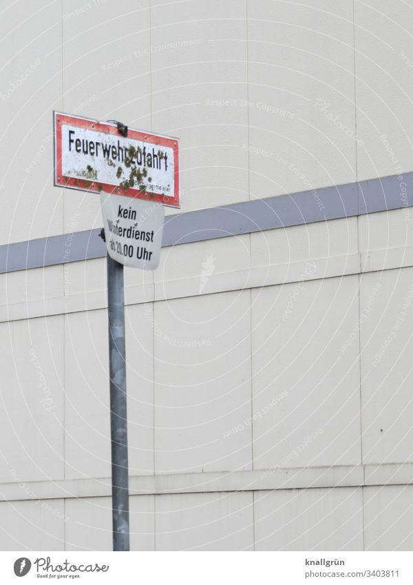 Dreckiges Feuerwehrzufahrt-Schild und Winterdienst-Schild vor einem öffentlichen Gebäude Kommunikation Schilder & Markierungen Hinweisschild Verkehrszeichen