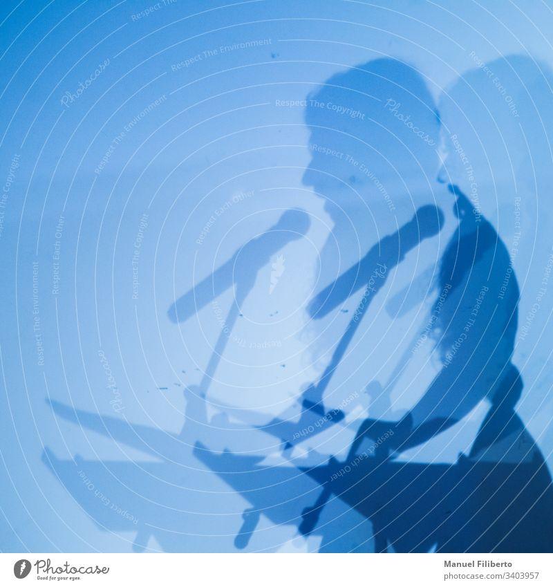 Doppelter Schatten einer Person, die durch ein Mikrofon auf einer blauen Wand spricht Rede Konzert Silhouette männlich Musik Party live Sitzung Leistung Pop