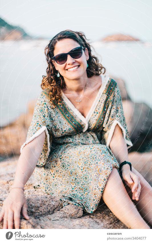 Porträt einer Frau mit Brille an einer Felsenküste Erwachsener attraktiv Hintergrund Strand schön Schönheit blau Brise Schlucht Kaukasier Küste Kleid Emotion