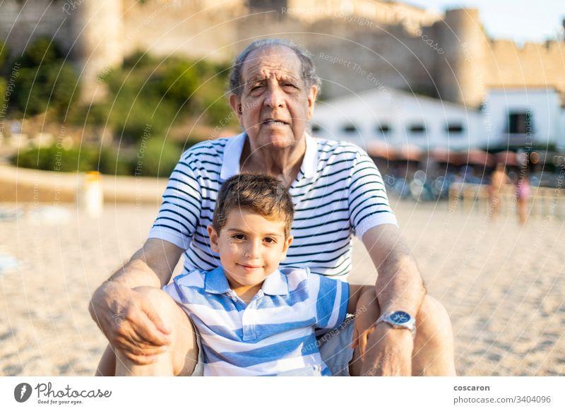 Porträt von Großvater und Enkel am Strand Junge Kaukasier heiter Kind Kinder Küste Genuss Familie Spaß Mädchen Enkelkind Enkelin Fröhlichkeit Glück habend