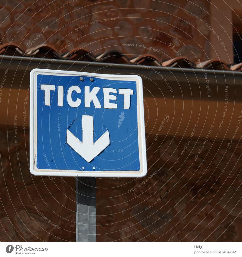 Ticket, Hinweisschild mit Pfeil nach unten vor einer Wand Schilder & Markierungen Außenaufnahme Fahrschein Verkehr blau weiß braun menschenleer quadratisch