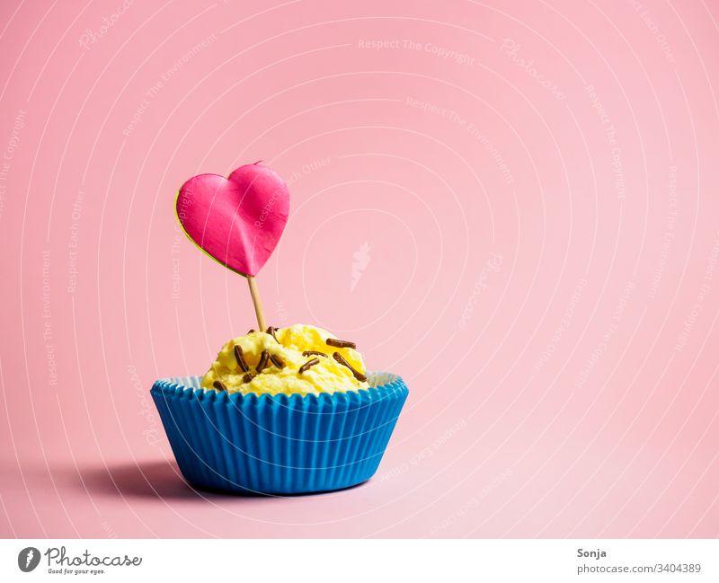 Vanilleeis in einer blauen Muffinform mit einem pinken Herzen auf einem rosa Hintergrund vanilleeis Eis muffinform herz Papier Farbfoto Sommer liebe geburtstag