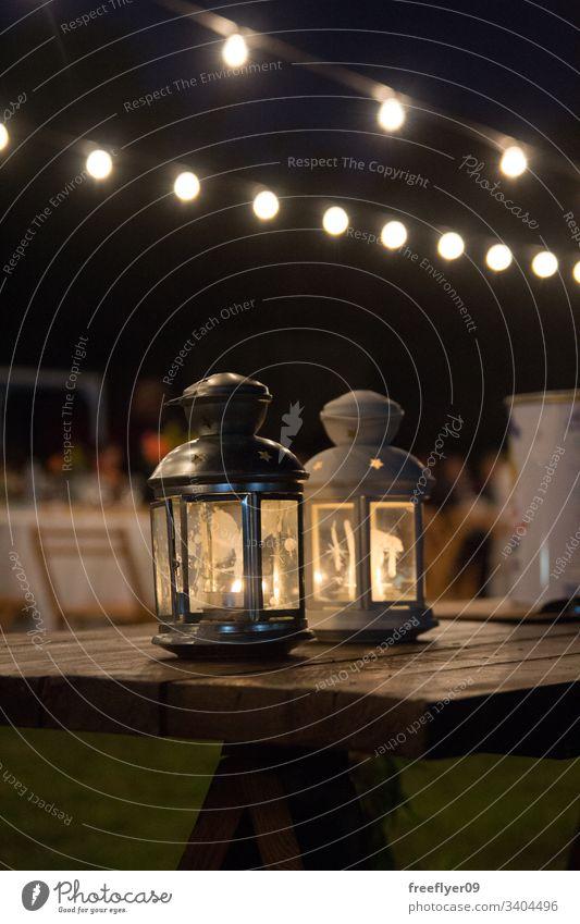 Laternen auf einem Holztisch bei einem Hochzeitsbankett im Freien hölzern Dekor Wand alt Cottage schäbig Dekoration & Verzierung beige Leuchter Design Details
