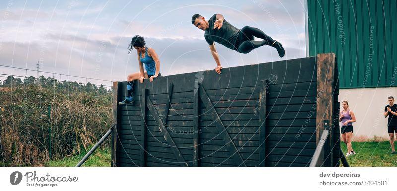 Teilnehmer des Hindernisparcours Kletterwand Hindernisrennen Mann Aufstieg Wand springend Überwindung OCR Transparente Netz Panorama panoramisch Fliege Läufer