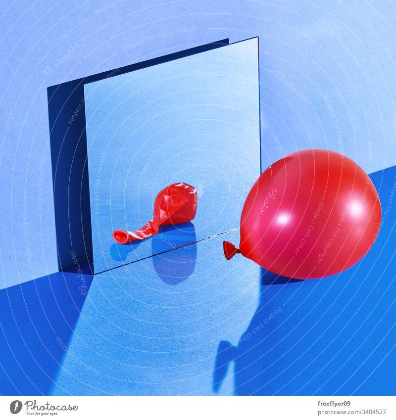 Stilleben im Raum mit einem geschwollenen Ballon, der sich in einem deflationierten Zustand widerspiegelt blau noch Stillleben hart Licht Spiegel Wand Quadrat