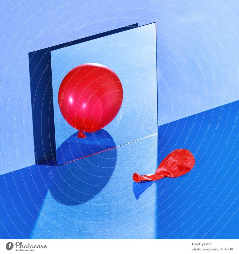 Stilleben im Raum mit einem entleerten Ballon, der auf einen geschwollenen Zustand reflektiert wird blau noch Stillleben hart Licht Spiegel Wand Quadrat