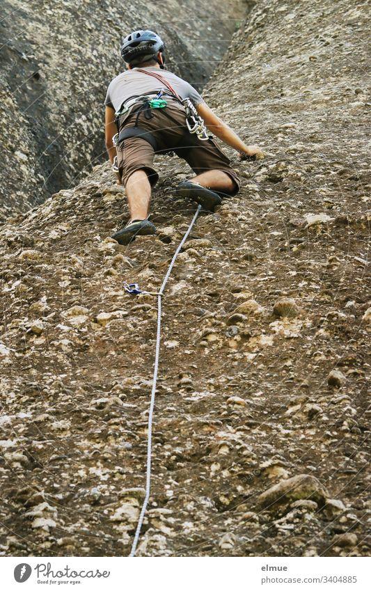 Kletterer an einer Felswand Boulder klettern bouldern Sport Freizeit & Hobby Lifestyle Mensch Freude Fitness junger Mann Sicherheit sichern Kraft Seil versuchen