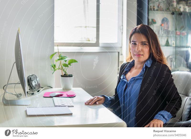Exekutive Frau in ihrem Büro mit großen Fenstern, durch die das Licht einfällt. Business Geschäftsfrau Computer Laptop jung Menschen Sitzen arbeiten