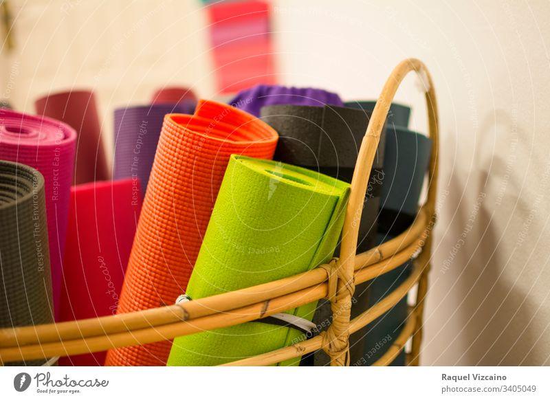 Weidenkorb mit mehreren Yogamatten oder gerollten Pilates in verschiedenen Farben. Unterlage Pilates-Sport Erholung Korb Lifestyle Gesundheit Gleichgewicht