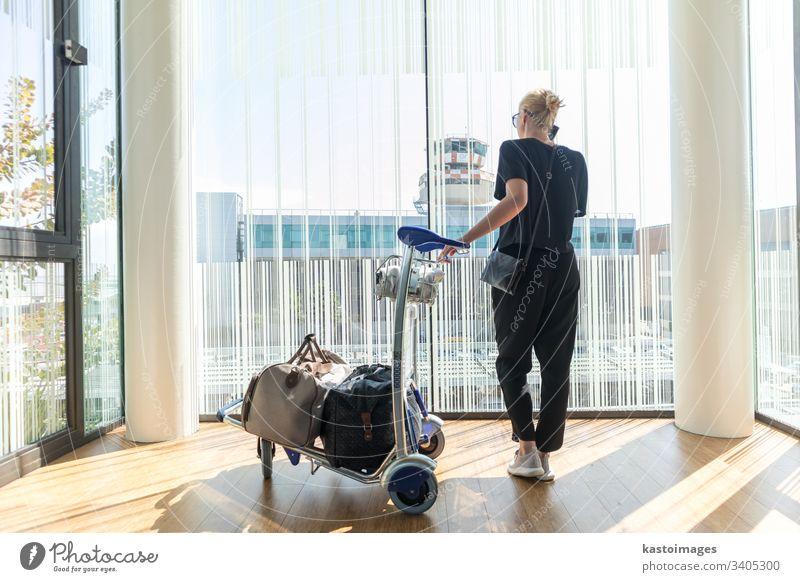Lässige Frau am Flughafenterminal, die am Handy telefoniert und auf den Abflug des Fluges mit Gepäck auf dem Gepäckwagen wartet. reisen Karre Abheben Telefon