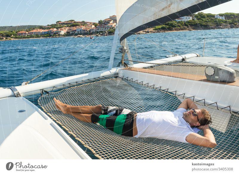 Sportlicher Mann entspannt sich, in der Hängematte eines Katamaran-Segelbootes liegend, auf luxuriösen nautischen Ferien in der Nähe der bildschönen Stadt Palau, Sardinien, Italien.