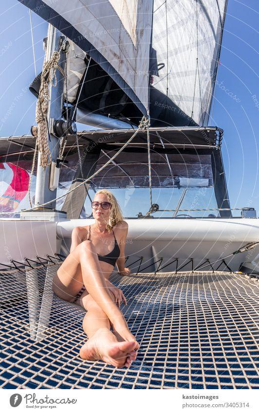 Frau entspannt sich auf einem Sommersegeltörn auf einem Luxuskatamaran in der Nähe der malerischen Stadt Palau auf Sardinien, Italien. Boot Katamaran Segeln