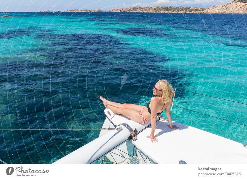 Frau entspannt sich auf einem Sommer-Segeltörn auf einem Luxus-Katamaran in der Nähe des bildschönen weißen Sandstrandes auf der Insel Spargi im Maddalena-Archipel, Sardinien, Italien.