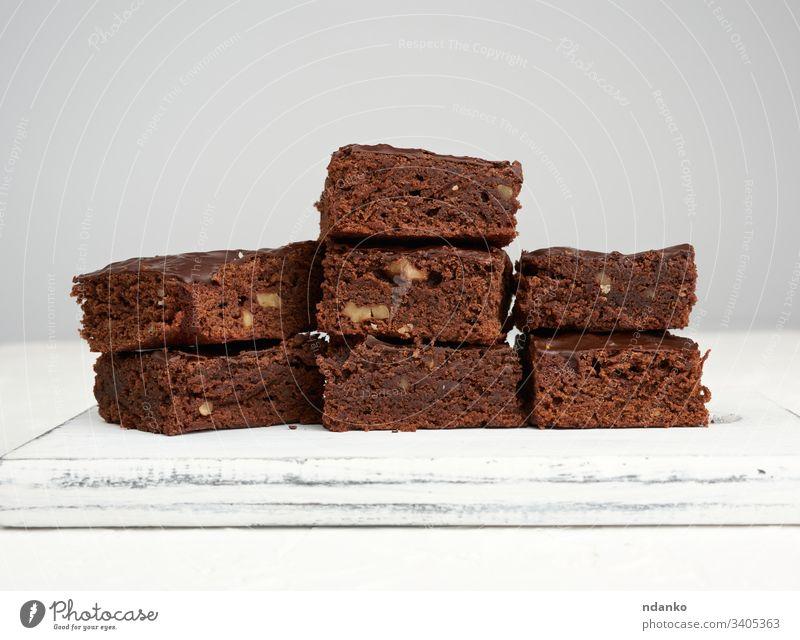 Stapel von quadratisch gebackenen Brownie-Schokoladenkuchenscheiben mit Walnüssen Bäckerei schwarz braun Kuchen Nahaufnahme Kakao Essen zubereiten Küche dunkel