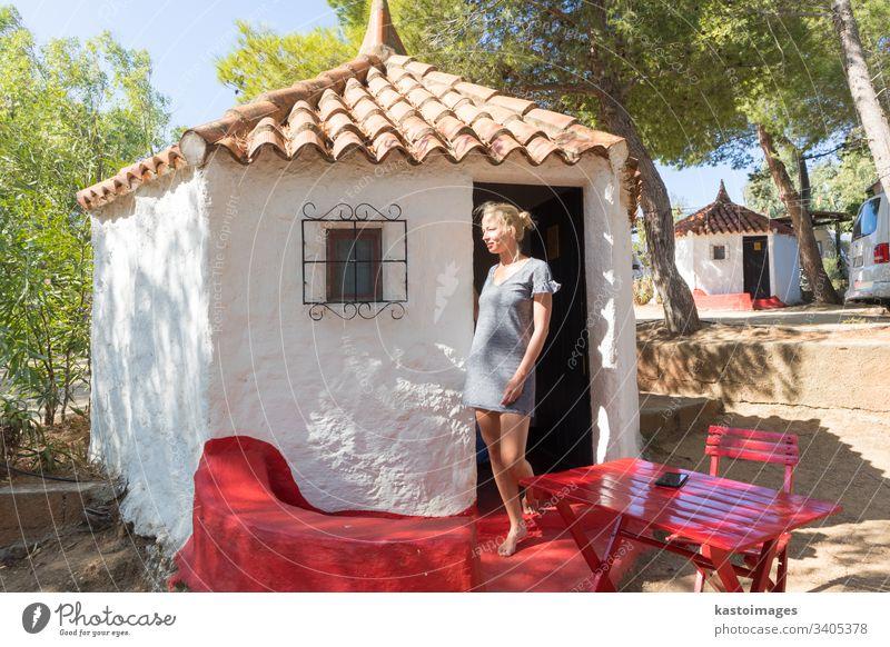 Frau genießt erholsame Sommerferien in einem authentischen Bungalow eines Campingdorfes unter mediterranen Kiefern, Palau, Sardinien, Italien. Haus Urlaub Glück