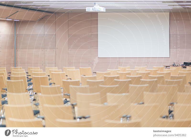 Leere Holzsitze in einem kotmportierten Hörsaal. Saal dozieren Aula Bildung leer Tagung Sitzung Präsentation Raum Stühle Schule weißer Bildschirm lernen