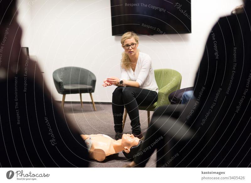 Ausbilder, der einen Erste-Hilfe-Kurs zur kardiopulmonalen Wiederbelebung und den Einsatz eines automatischen externen Defibrillators in einem HLW-Workshop unterrichtet.