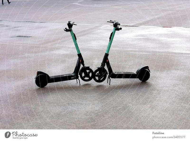 Fluch oder Segen? - oder zwei E-Scooter stehen auf einem betonierten Platz und ganz oben links in der Ecke läuft der Benutzer aus dem Bild Farbfoto