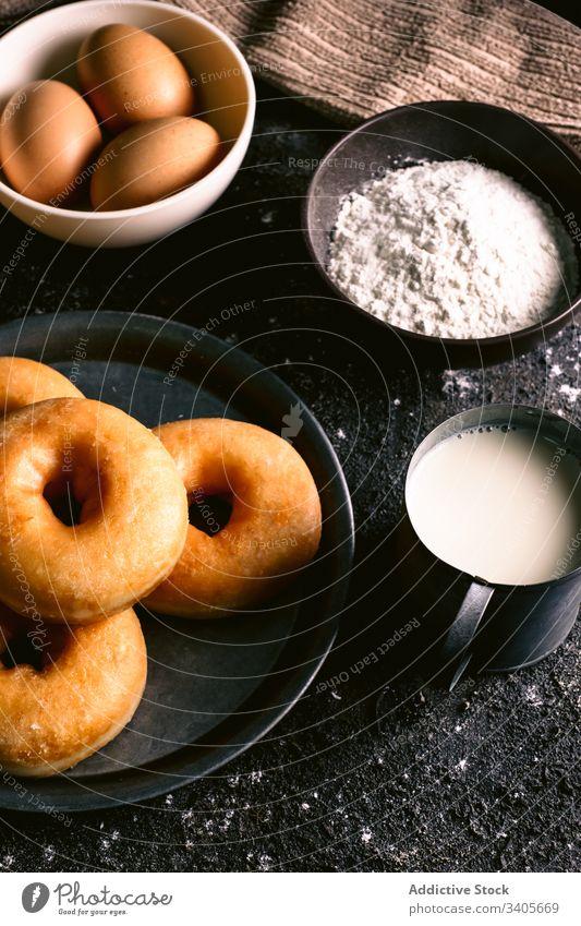 Doughnuts in der Nähe von Zutaten auf dem Tisch Bestandteil Koch Küche Rezept Mehl melken Ei Utensil Gebäck Lebensmittel Serviette Löffel geschmackvoll lecker