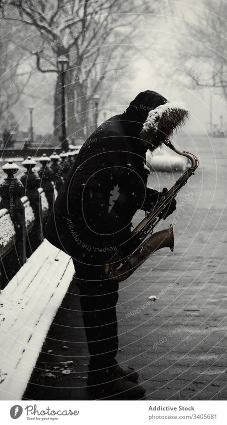 Anonymer Mann mit Saxophon auf Stadtstraße spielen Winter Straße Großstadt modern Jacke Musik Melodie Klang Instrument männlich unterhalten Lifestyle Saison
