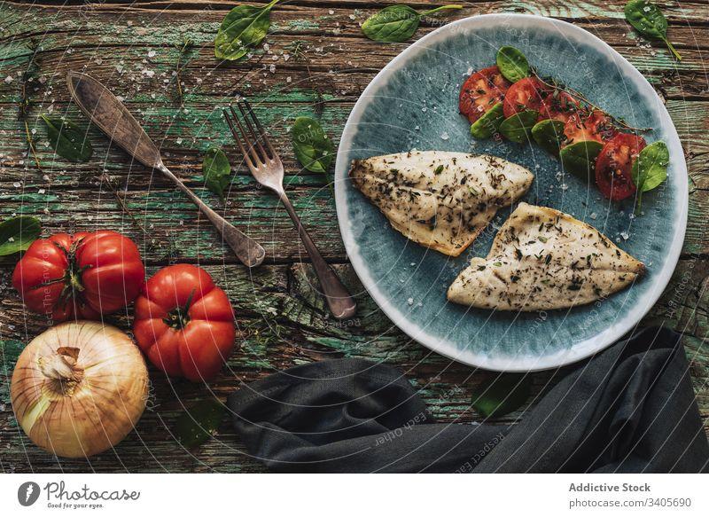 Gebratener Fisch mit Kräutern und Gemüse Kraut Speise Tisch Basilikum Filet Teller schäbig hölzern frisch Lebensmittel geschmackvoll Mahlzeit Tomate Zwiebel