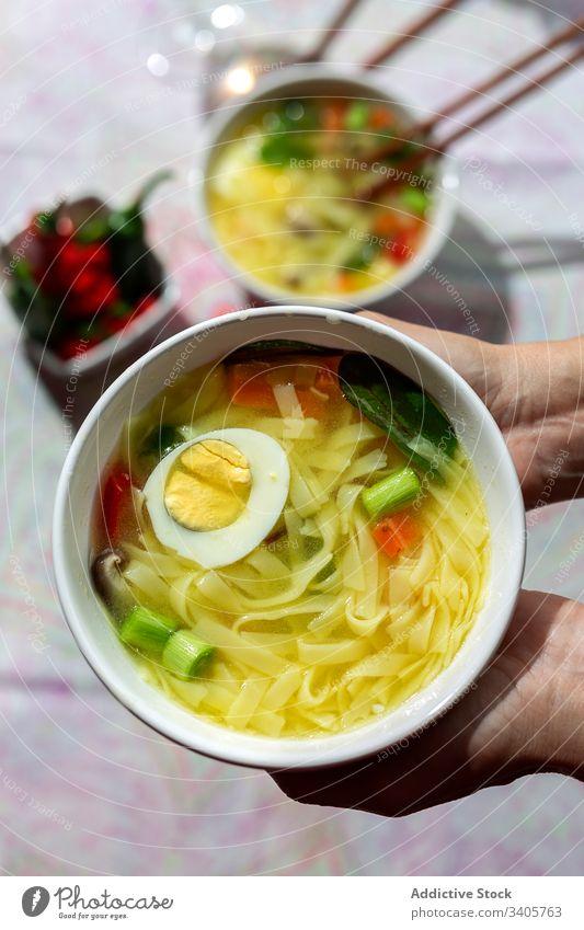 Anonyme Person, die in einem Restaurant eine Schüssel Nudelsuppe hält Lebensmittel Ramen Nudeln Suppe asiatisch Chinesisch Vegane Ernährung Gemüse Vegetarier