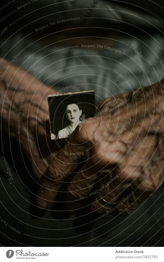 Nicht erkennbare ältere Person mit altem Foto Gedächtnis erinnern in den Ruhestand gehen dunkel Nostalgie ruhig Bild Papier gealtert Senior reif Rentnerin