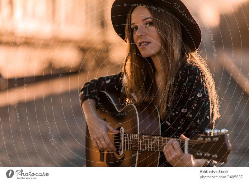 Frau spielt Gitarre auf Schienen spielen Musik reisen Stil ausführen Landschaft Instrument akustisch Musiker Gesang unterhalten Hut Boho Klang Melodie Lifestyle