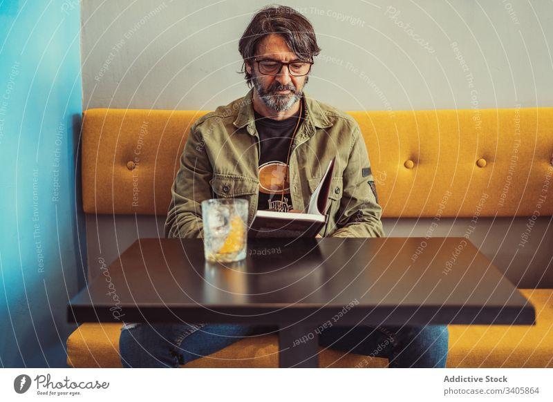 Bärtiger Mann liest Buch im Cafe lesen Café Sofa Tisch Cocktail ernst sitzen männlich lässig modern Lifestyle reif Erwachsener sich[Akk] entspannen ruhen Bar
