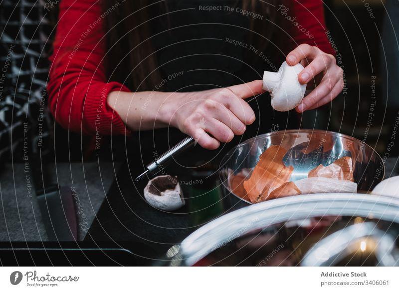 Nutzpflanzenfrau schneidet Pilze über Schüssel Frau geschnitten Küche Kurs Sauberkeit Koch Restaurant Tisch Schalen & Schüsseln Messer vorbereiten Lebensmittel
