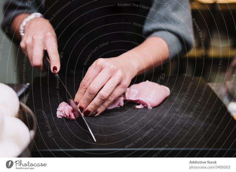 Erntehelfer beim Schneiden von Hühnerbrust Person geschnitten Hähnchen Tisch Küche Restaurant Koch Kurs Messer vorbereiten frisch Küchenchef Bestandteil Prozess