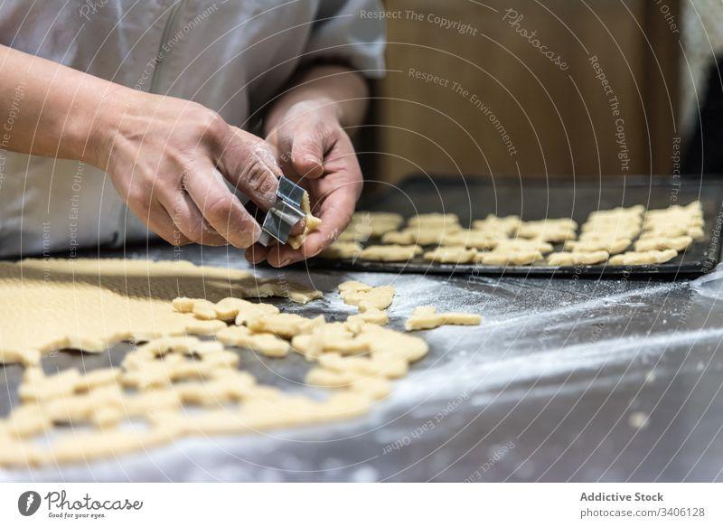 Getreidebäcker, der Kekse auf dem Tisch backt Bäcker geschnitten Bäckerei Teigwaren Mehl Koch Küchenchef Arbeit Kutter Werkzeug Lebensmittel Gebäck Bestandteil