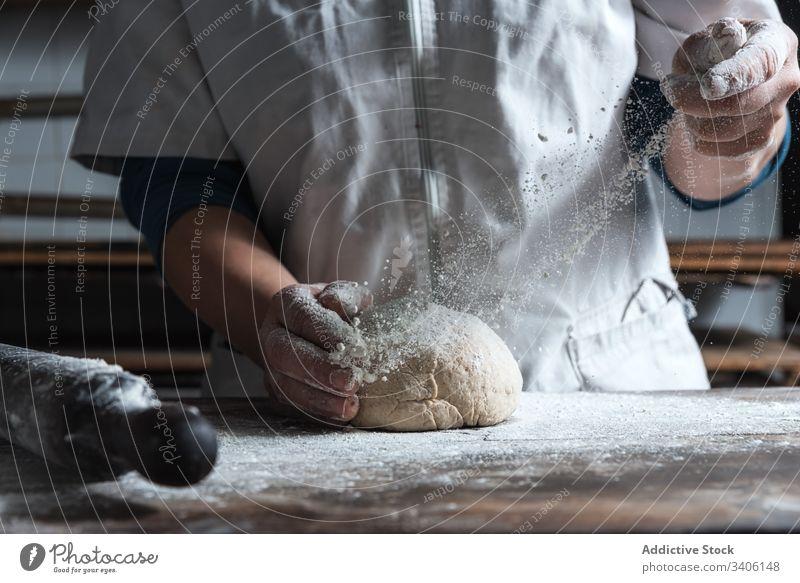 Getreidebäcker, der den Teig auf dem Tisch knetet Bäcker kneten Teigwaren Mehl Bäckerei Koch Küche Bestandteil Lebensmittel vorbereiten Brot Arbeit Job