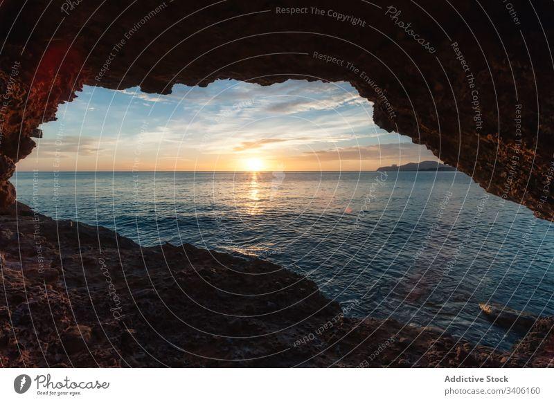 Raue Höhle in Meeresnähe bei Sonnenuntergang MEER Himmel Ufer Eingang rau Mütze des Falken Ibiza Spanien Wasser Natur Küste Landschaft malerisch Felsen Abend