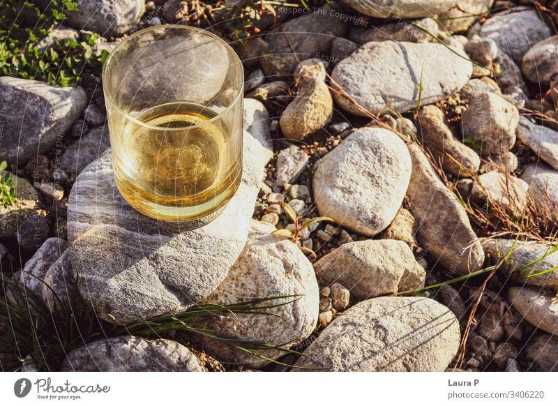 Nahaufnahme eines Glases mit Whisky auf einigen Steinen abschließen Whiskey Rum Alkohol Getränk Bourbon trinken Natur Konzept sich[Akk] entspannen Erholung